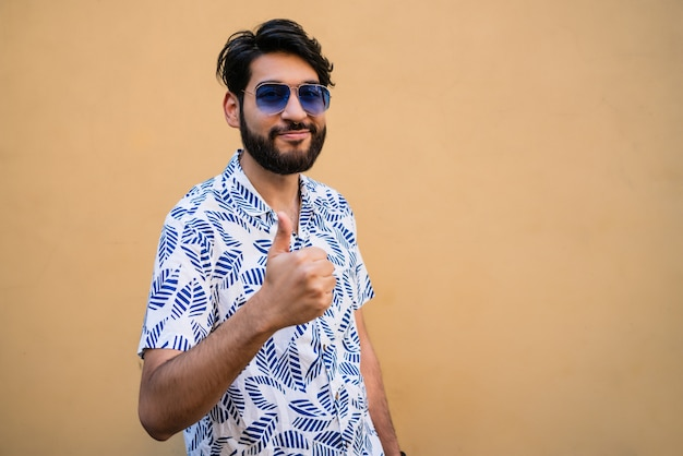Portrait of young man with summer clothes and thumbs up against yellow space.