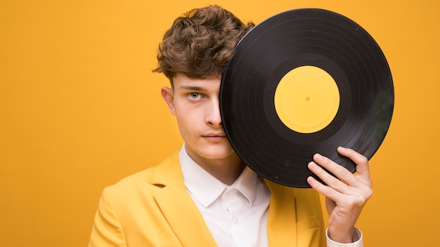 Portrait of young man with a vinyl in a yellow scene