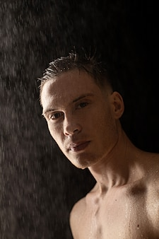 Portrait of young man with water drops on black wall