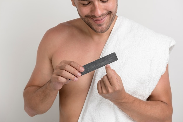 Portrait of young man with white towel polishing his nails with fine