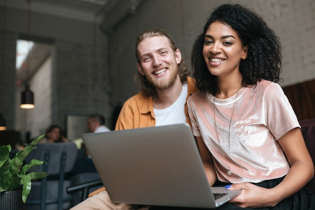 Portrait of young man and woman sitting at the restaurant and happily looking in camera with laptop in hands