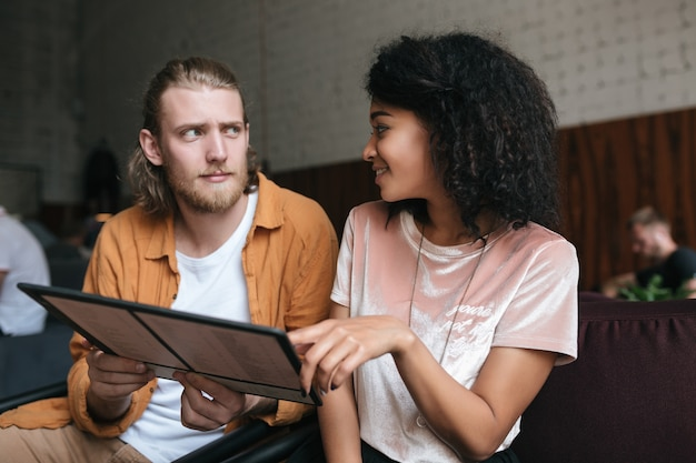 Portrait of young man and woman sitting in restaurant with menu in hands