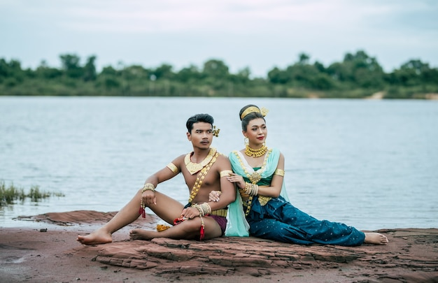 Portrait of young man and woman wearing traditional costume posing in nature in thailand