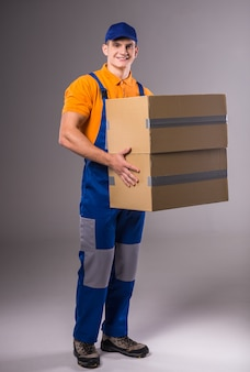 Portrait of a young man in work clothes with boxes.