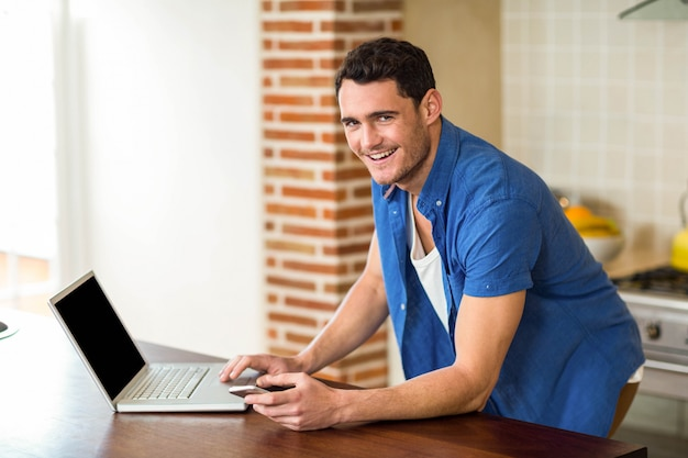 Portrait of young man working on laptop in kitchen