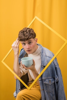 Portrait of young man  in a yellow scene behind a frame
