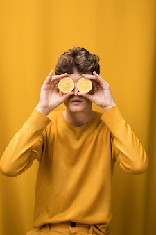 Portrait of young man  in a yellow scene with lemon slices in front of eyes
