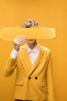 Portrait of young man  in a yellow scene with torn paper in front of face