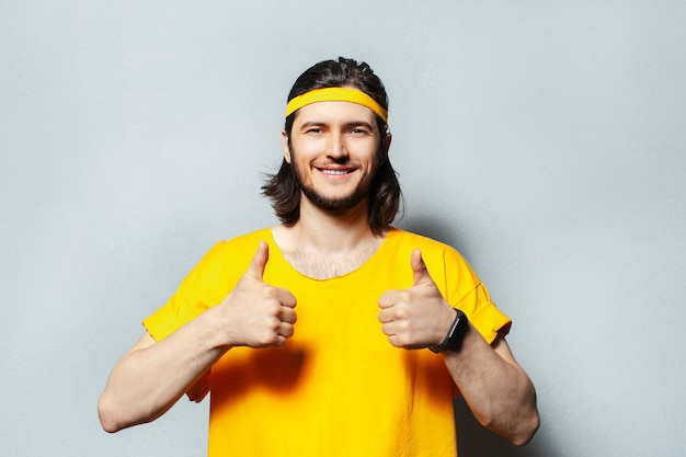 Portrait of young man in yellow shirt showing thumbs up.