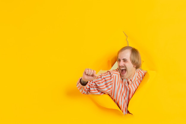 Portrait of young man on yellow torn breakthrought background