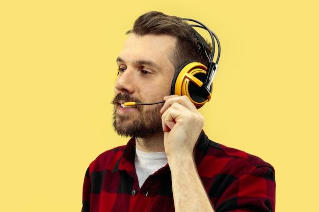 Ritratto di giovane uomo sulla parete gialla.