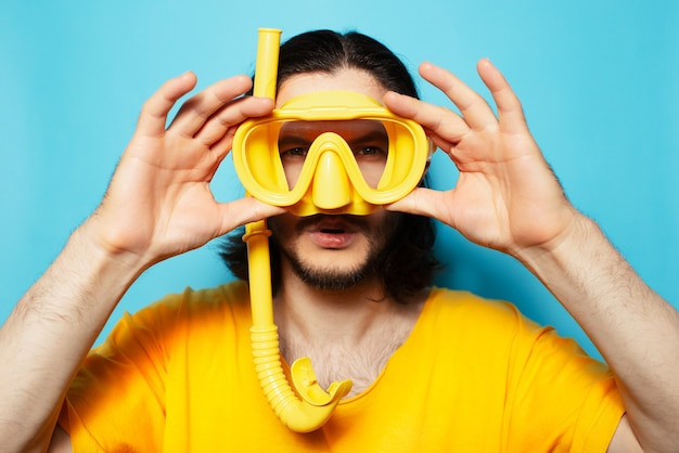Portrait of young man in yellow, wearing diving mask and snorkel