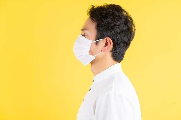 黄色の上に立っている肖像画の若い仮面の男