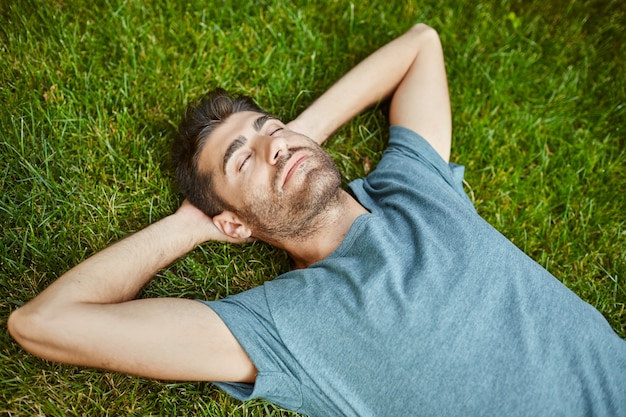 Portrait of young mature good-looking caucasian man in blue shirt peaceful lying on grass with yes closed.