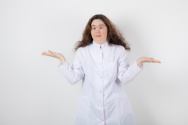 Portrait a young model girl with down syndrome standing with white uniform.