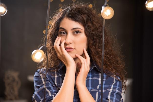 Ritratto di una giovane modella in plaid che si mette le mani sul viso