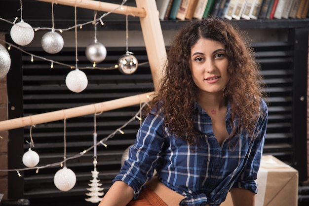Portrait of a young model in plaid shirt posing near christmas balls