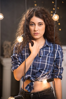 Portrait of a young model in plaid shirt posing near lamps