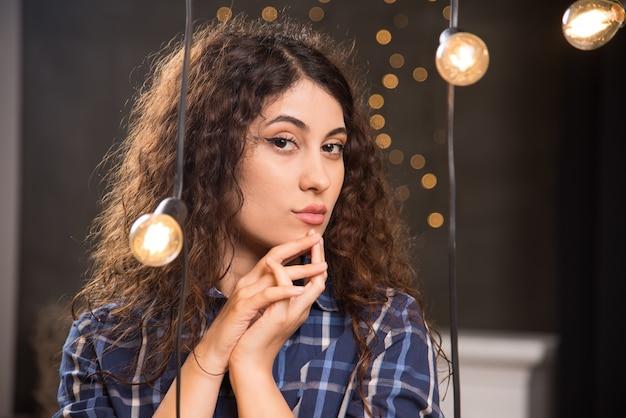 Ritratto di una giovane modella in camicia a quadri in posa vicino alle lampade