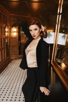 Portrait of a young model woman with perfect makeup and full red lips wearing a satin blouse and a trendy suit posing at the luxurious interior