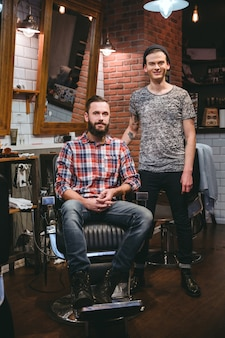 Portrait of young modern barber and his handsome content bearded client in barbershop