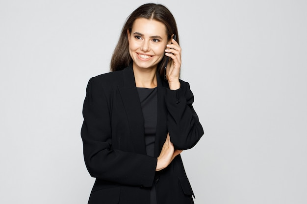 Portrait of young modern business woman in classic suit talking on smartphone