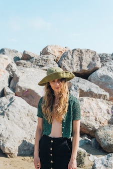 Portrait of young modern woman with hat on her head standing near beach rocks