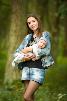 Portrait of a young mom with a baby on the street. baby on the hands of a young smiling mom in a spring alley.