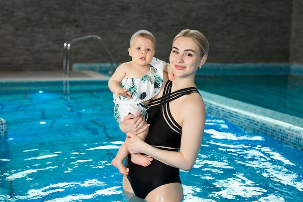 Portrait of a young mother and baby daughter in the pool after a workout.