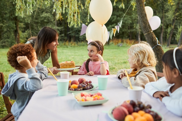 Portrait of young mother bringing birthday cake to smiling girl during birthday party outdoors copy ...