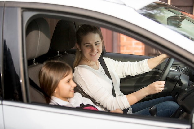 Portrait of young mother driving car to school with daughter