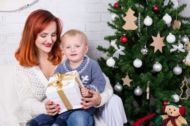 Portrait of young mother and little son sitting in front of christmas tree