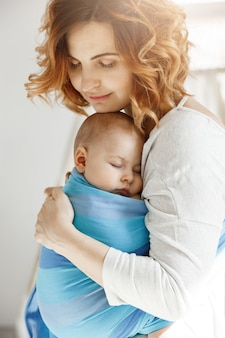 Portrait of young mother and newborn son sleeping on mother chest in blue baby sling. family happiness vibes. family concept.