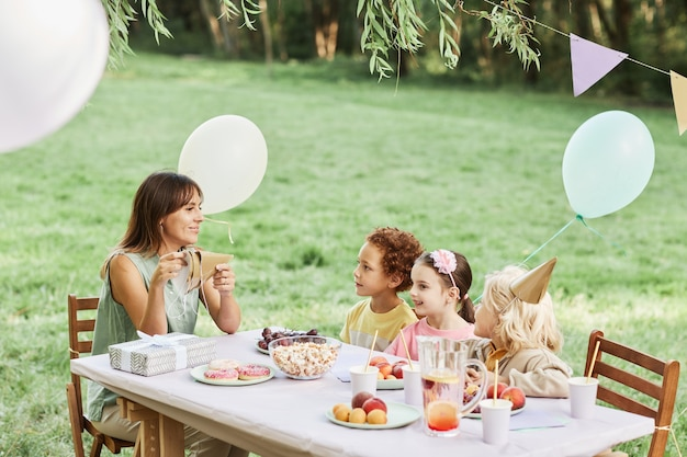 Portrait of young mother sitting at picnic table with group of kids during outdoor birthday party in...
