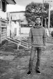 Portrait of young multi ethnic asian man in the streets outdoors in black and white