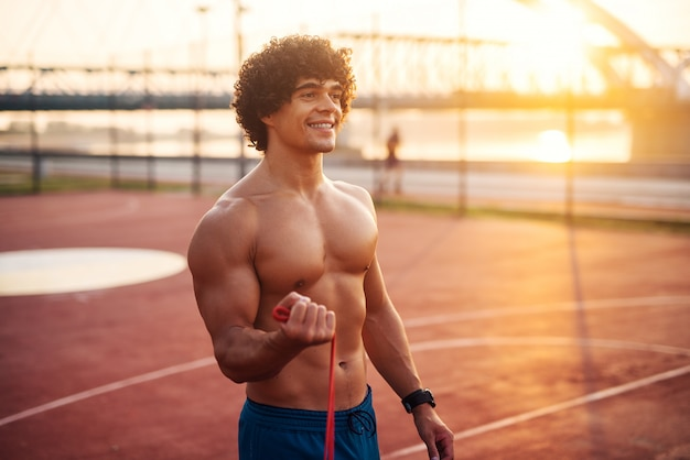 Portrait of young muscular happy man training outside early in the morning