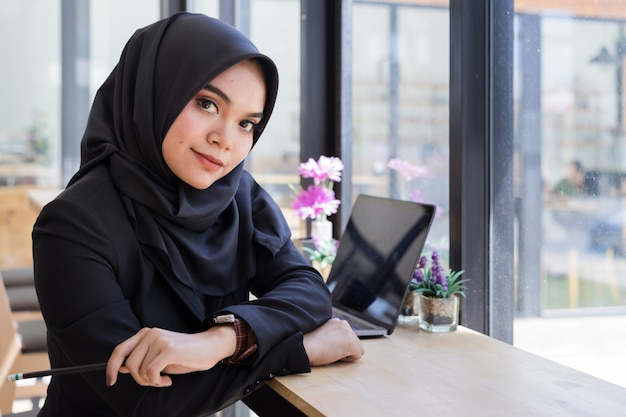 Portrait of young muslim business people wearing black hijab, working in coworking.