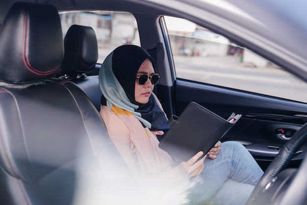 Portrait of a young muslim business woman reading in the back seat of the car.