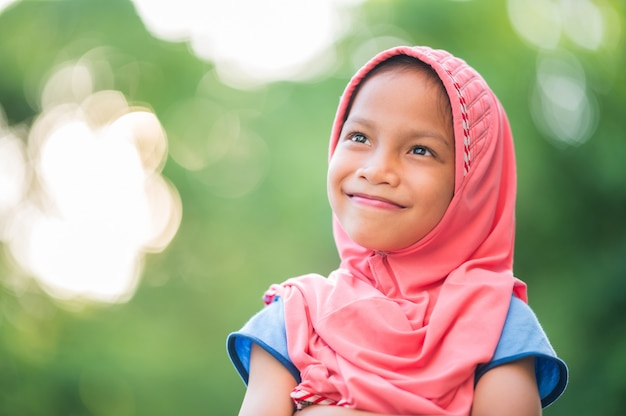Portrait of a young muslim girl, covered with red cloth, smiling, happy and copy space