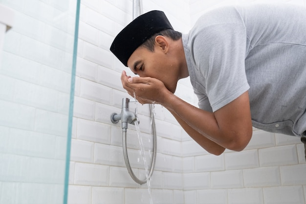 Portrait of young muslim man perform ablution gargle (wudhu) before prayer at home
