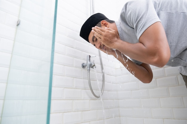 Portrait of young muslim man perform ablution (wudhu) before prayer at home