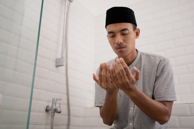 Portrait of young muslim man praying after perform ablution  at the bathroom
