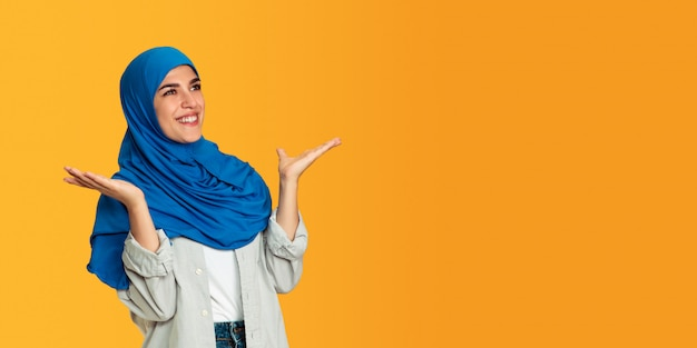 Portrait of young muslim woman isolated on yellow studio background