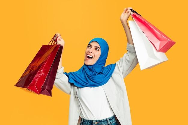 Ritratto di giovane donna musulmana isolata sul muro giallo
