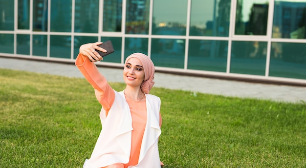 Portrait of young muslim woman posing taking selfie photo with mobile phone outdoor