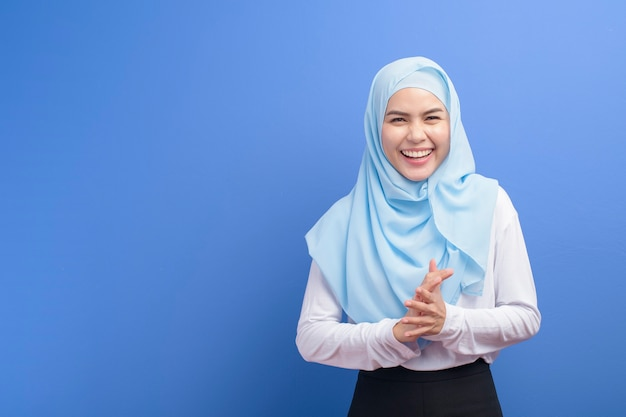 Portrait of a young muslim woman with hijab over blue background studio.