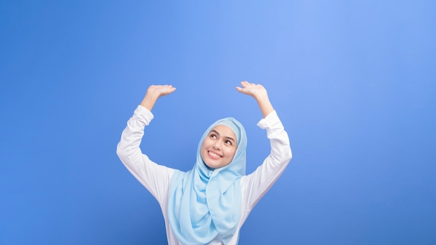 Portrait of a young muslim woman with hijab over blue