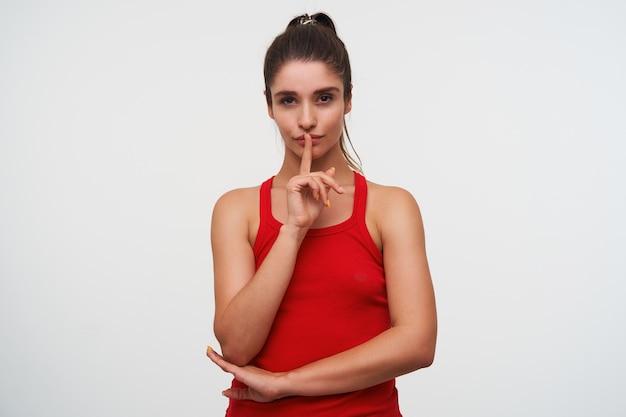 Ritratto di giovane donna misteriosa carina bruna indossa in maglietta rossa mostra gesto di silenzio, per favore mantieni la calma. si trova su sfondo bianco.