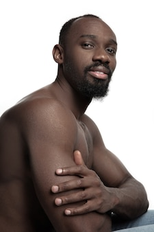 Portrait of a young naked happy smiling african man at studio. high fashion male model posing and isolated on white background