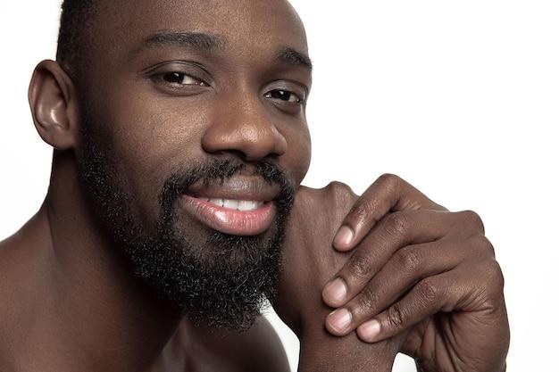 Ritratto di un giovane uomo africano sorridente felice nudo in studio.